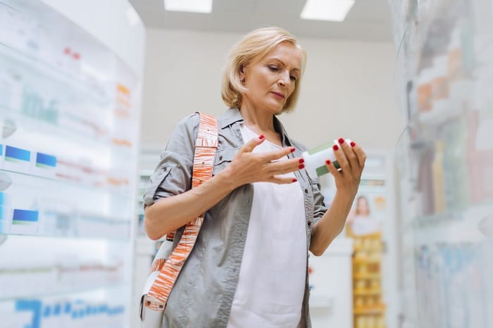 Attentive blonde aged woman looking at vitamins
