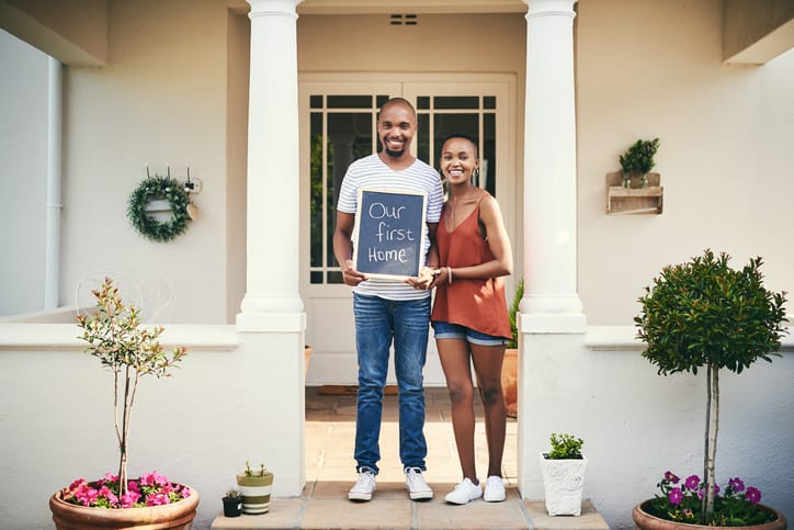 "Portrait of a young couple holding a chalkboard with ""our first home"" written on it"